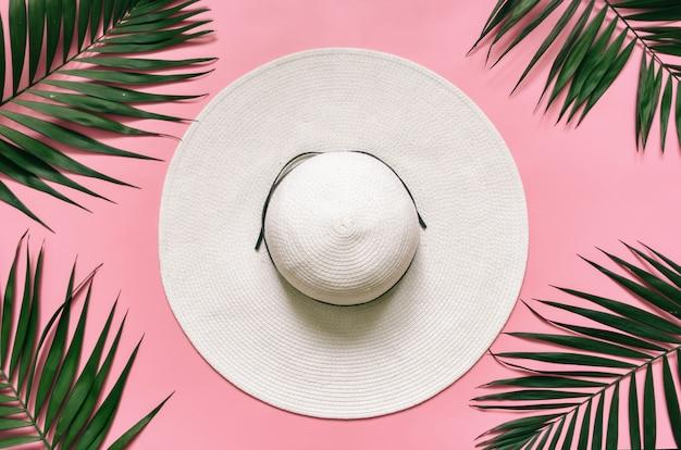 Biały słomkowy kapelusz i zielone liście palmowe ułożone na jasnoróżowym tle