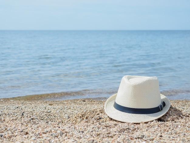 Biały słomkowy kapelusz leży na piasku plaży na tle morza