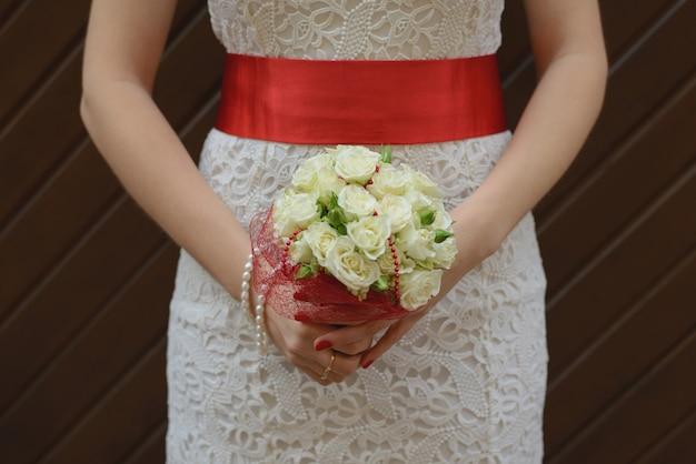 Biały ślubny bukiet róż w rękach panny młodej, dziewczyny w białej sukni z czerwoną satynową tasiemką w dłoniach