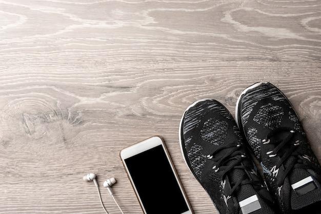 Biały smartfon ze słuchawkami na drewnianym stole