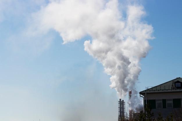 Biały smog z fabrycznej rury na niebie