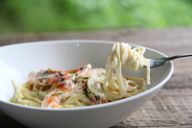 Biały sos do spaghetti z krewetkami na tle drewna