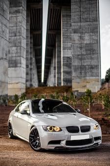 Biały sportowy samochód stojący pod mostem.