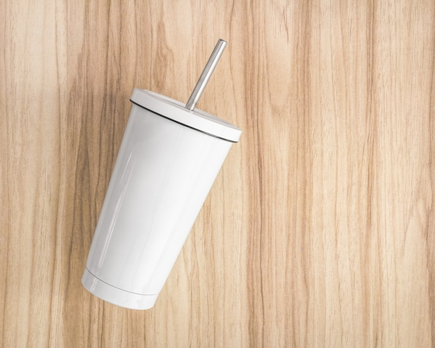 Biały stalowy kubek z tubką na drewnianym tle. izolowany pojemnik na napoje.