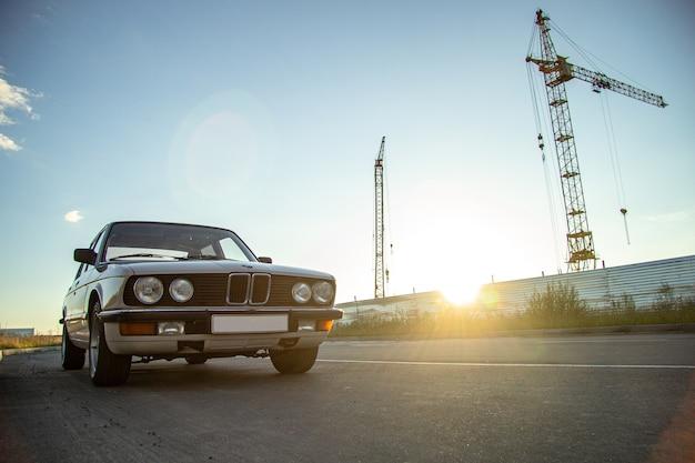 Biały starodawny klasyczny samochód z okrągłymi reflektorami na drodze podczas zachodu słońca