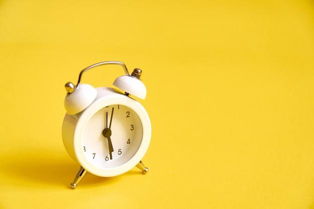 Biały stary budzik na kolorze żółtym