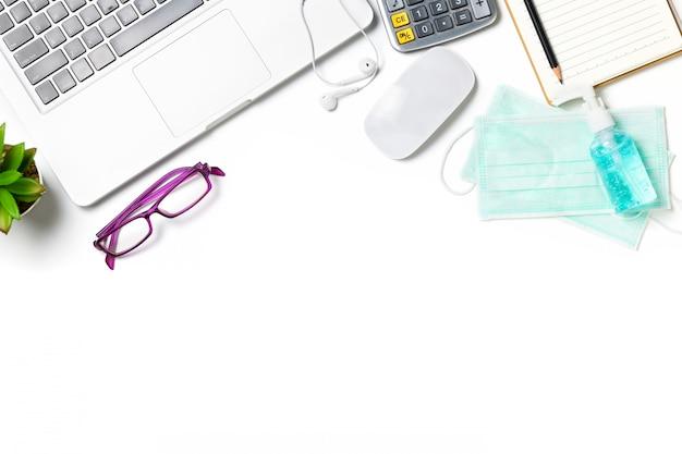 Biały stół biurkowy z chirurgiczną maską na twarz i środkiem dezynfekującym lub żelem alkoholowym z laptopem
