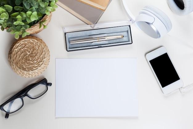 Biały stół biurkowy z dużą ilością rzeczy, widok z góry