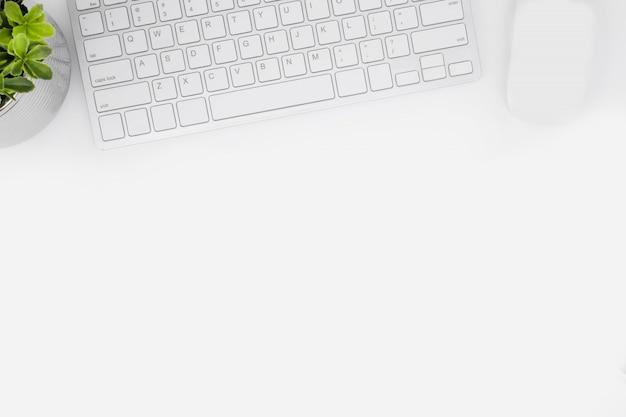 Biały stół biurkowy z gadżetami komputerowymi.