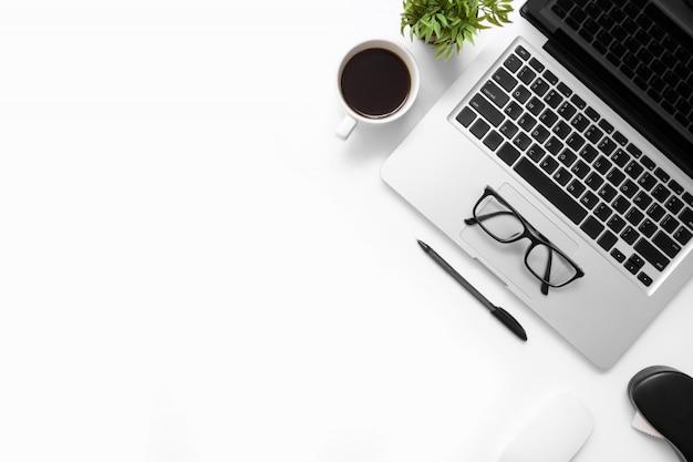 Biały stół biurowy z gadżetami komputerowymi, filiżanką kawy i innymi artykułami biurowymi.