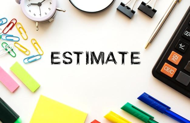 Biały stół biurowy z kalkulatorem, kolorowymi długopisami i innymi artykułami papierniczymi. tekst na estimate