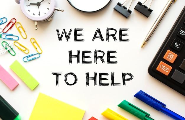 Biały stół biurowy z kalkulatorem, lupą, kolorowymi długopisami i innymi artykułami papierniczymi. tekst na stronie jesteśmy tutaj pomóc. widok z góry. pomysł na biznes.