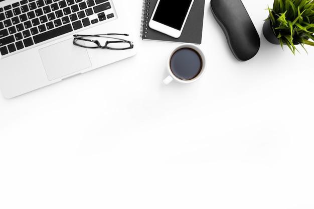 Biały stół biurowy z laptopem i artykułami biurowymi.