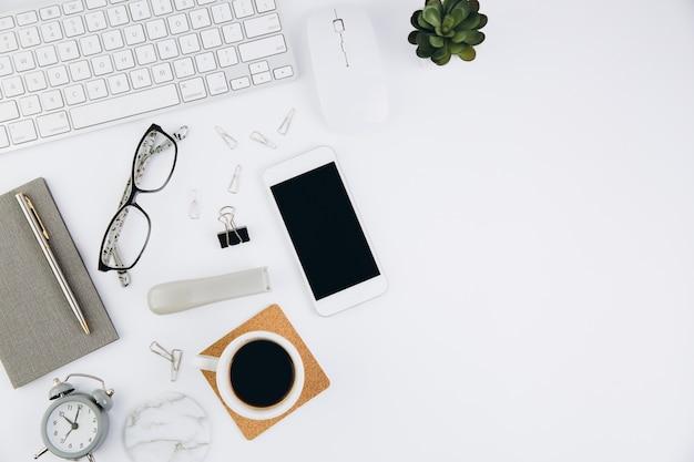 Biały stół biurowy z notebookiem, klawiaturą i innymi artykułami biurowymi
