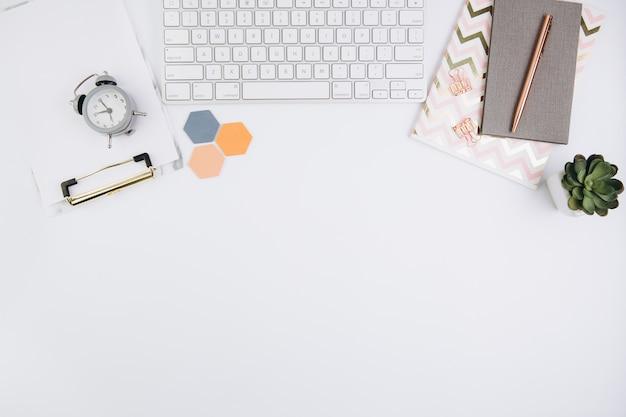 Biały stół biurowy z notebookiem, klawiaturą komputerową i innymi artykułami biurowymi