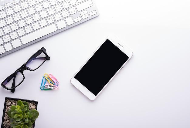 Biały stół biurowy z rośliną, smartfonem, okularami i klawiaturą