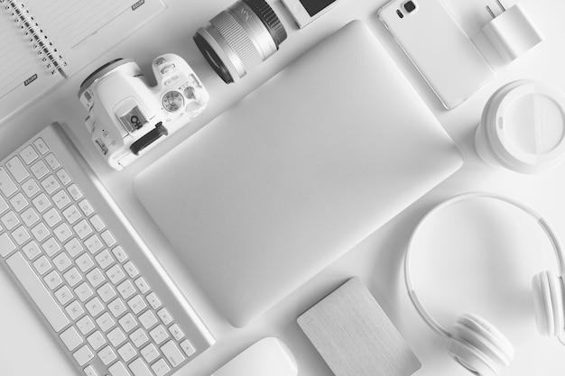Biały stół biurowy z wieloma białymi gadżetami