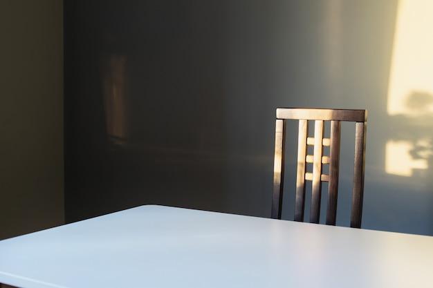 Biały stół i drewniane krzesło na tle szarej ścianie w słońcu