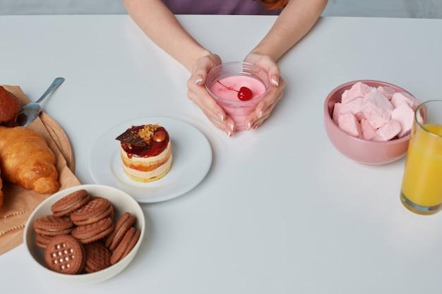 Biały stół kuchenny z rogalikami, ciastkami, ciastami i produktami do pieczenia