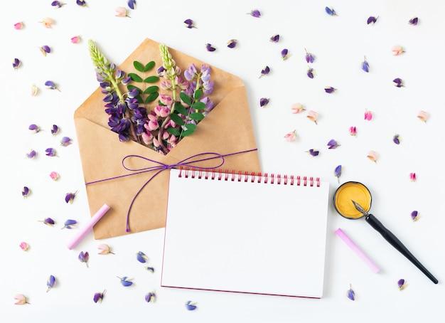 Biały stół leży koperta, notatnik, pióro i kwiaty