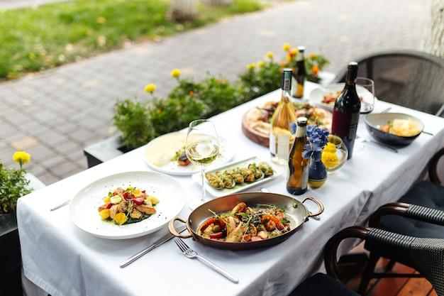 Biały stół podawany z pysznym włoskim jedzeniem z owocami morza na patelni