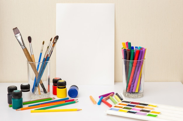 Biały stół z kolorowymi przyborami do rysowania i białym papierem. pędzle, akwarele, kredki, ołówek, farby akrylowe. pojęcie kursów rysunkowych. makieta