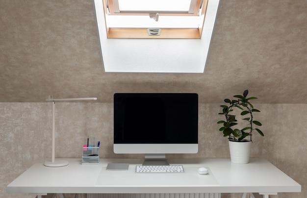 Biały stół z monitorem, lampą stołową i rośliną domową. domowe biuro