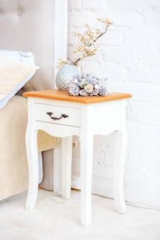 Biały stolik nocny. wazon dekoracyjny koncepcja wnętrza