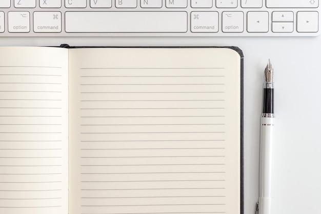 Biały stolik z notatnikiem, klawiaturą i wiecznym piórem. widok z góry