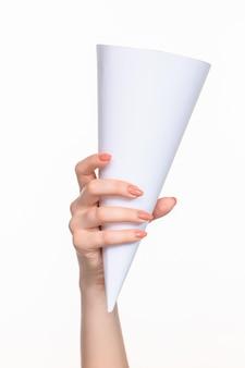 Biały stożek rekwizytów w kobiecych rękach na białym tle