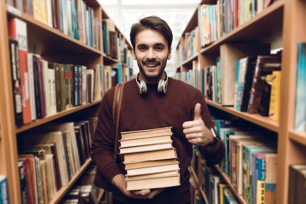 Biały student w swetrze z książkami w nawie biblioteki.