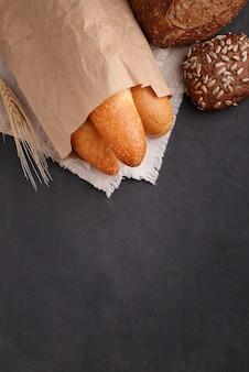 Biały, szary i chleb żytni, bagietka, rolka z sezamem na czarnym tle