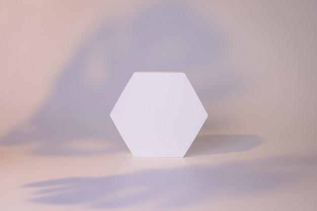 Biały sześciokąt na białym tle z cieniami liści. makieta do prezentacji produktu, kosmetyku, urody. minimalna scena.
