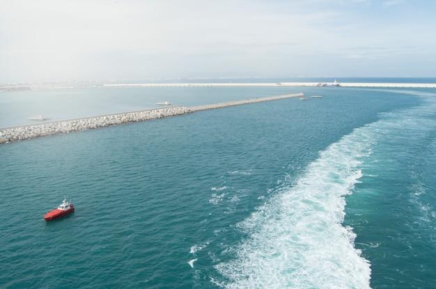 Biały szlak, piana i fale na morzu śródziemnym za liniowcem wypływającym z portu w walencji, widok na port, latarnię morską, falochron
