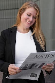 Biały t-shirt odzież plus rozmiar bizneswoman czyta gazetę