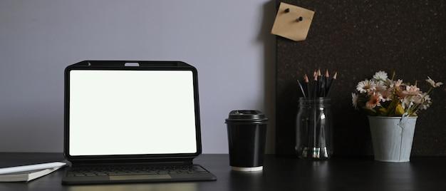 Biały tablet z pustym ekranem kładzie się na biurku otoczonym różnymi urządzeniami.