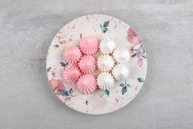 Biały talerz biało-różowych cukierków bezowych na kamiennym stole.