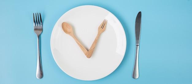 Biały talerz ceramiczny z nożem, łyżką i widelcem na niebieskim tle. koncepcja przerywanego postu