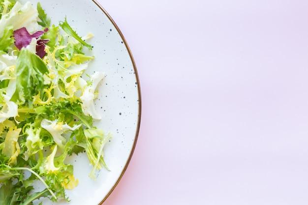 Biały talerz ceramiczny ze świeżą sałatą na jasnoróżowej powierzchni