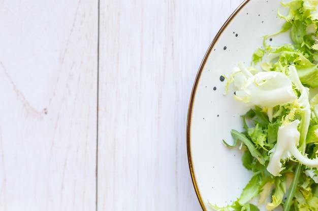 Biały talerz ceramiczny ze świeżą sałatką na drewnianej powierzchni