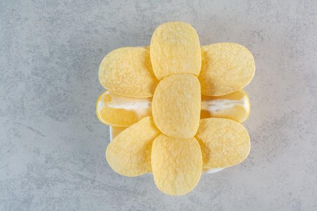 Biały talerz chrupiących chipsów ziemniaczanych na szaro.