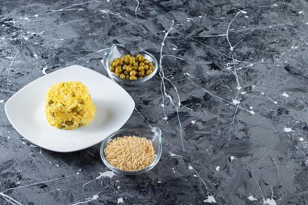 Biały talerz gotowanego na parze ryżu z zielonym groszkiem na tle marmuru.