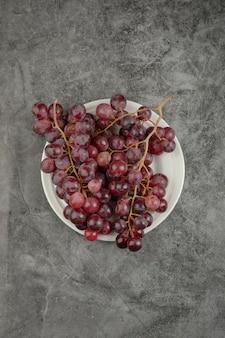 Biały talerz i czerwone pyszne winogrona na marmurowym stole.