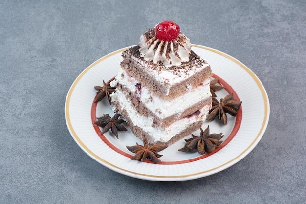 Biały talerz kawałka ciasta i anyżu gwiazdkowatego
