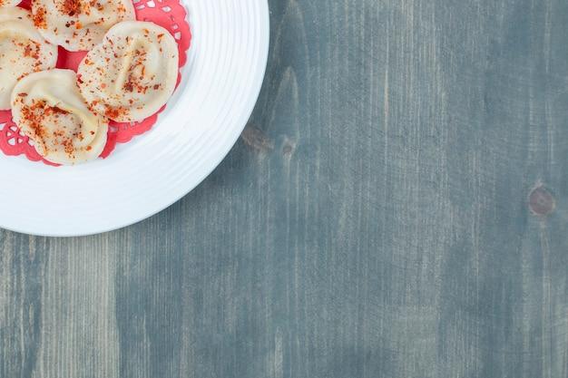 Biały talerz klusek gotowanych mięsem na drewnianej powierzchni.