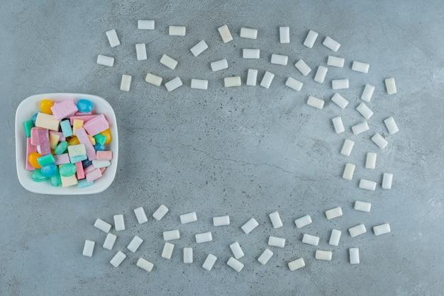 Biały talerz kolorowych gum balonowych na kamiennej powierzchni.