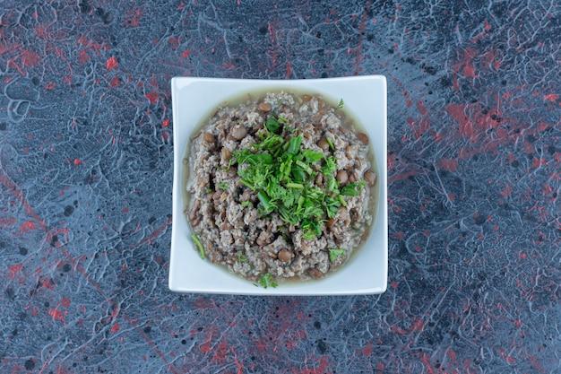 Biały talerz mięsa mielonego z groszkiem i ziołami.