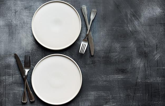 Biały talerz na ciemnym stole z kamienia. ustawienie tabeli.