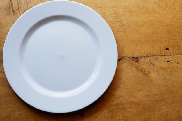 Biały talerz na drewnianym stole z miejscem na kopię