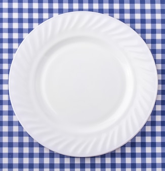 Biały talerz na niebieskim i białym tle obrus tkaniny w kratkę.
